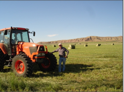 Rancher with new tractor and bales in background
